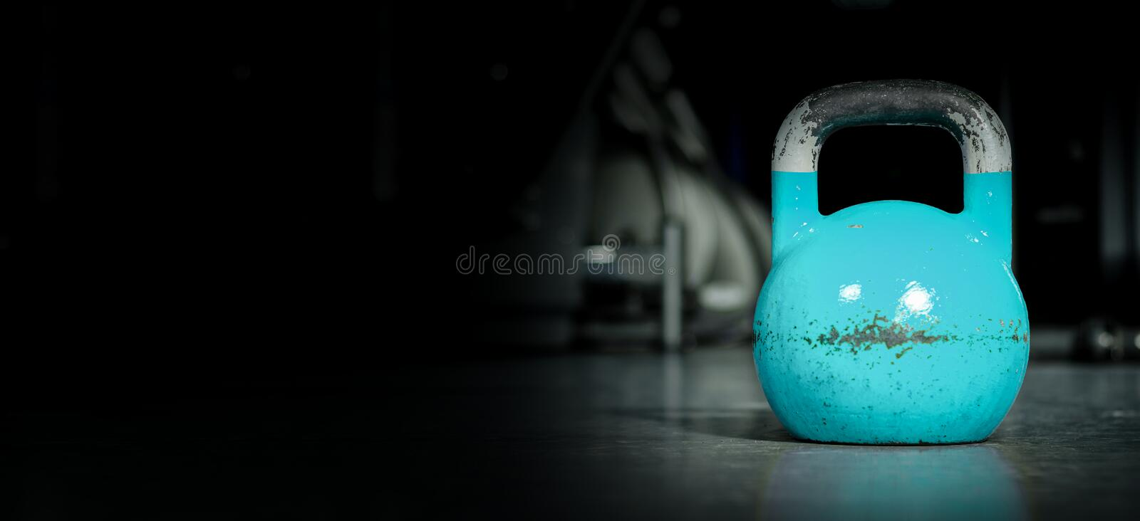 Kettle bell sport, Heavy old used color kettlebell weight on the gym floor ready for fitness strength workout. To build muscles with dark background and free stock image