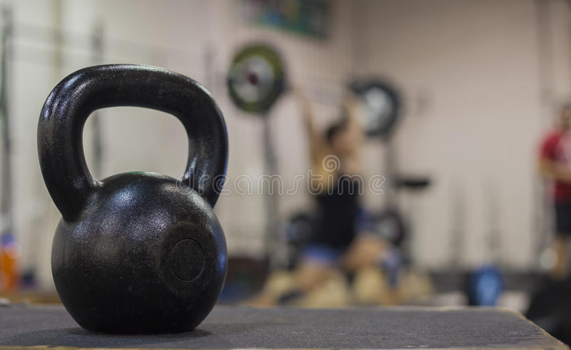 A cast iron kettle bell with a young women weight lifting in the background. A posed photo of a cast iron kettle bell with blured a young woman doing olympic stock photography