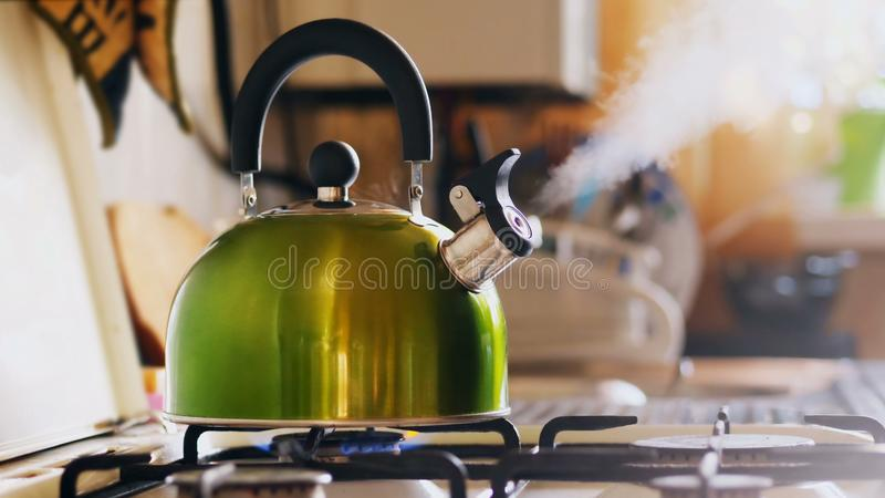 Kettle Boiling On a Gas Stove. Boiling green kettle boiling with steam emitted from spout. Shallow depth of field. Solar glare from the kitchen window royalty free stock image