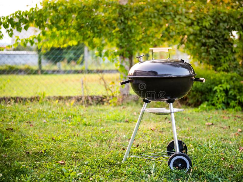 Kettle Charcoal BBQ Barbecue Grill in garden or backyard. Side View of Black Kettle Grill with cover in home front or backyard and green lawn. Portable BBQ stock photos