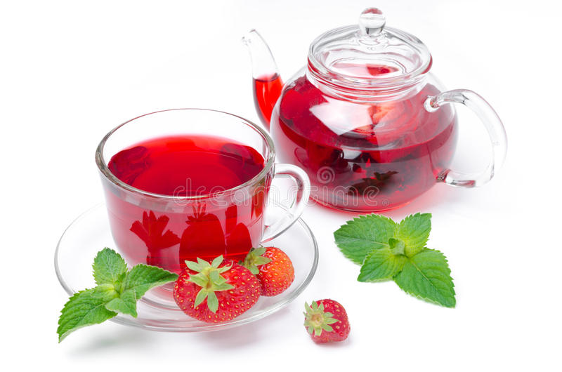 Kettle and a cup of red tea with strawberries and mint isolated royalty free stock image