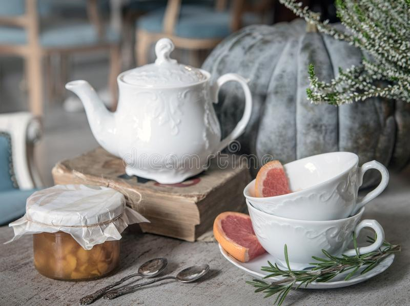 Kettle, jam, old book and wo tea cups with rosemary and grapefruit on the background of a large pumpkin and heather. stock images