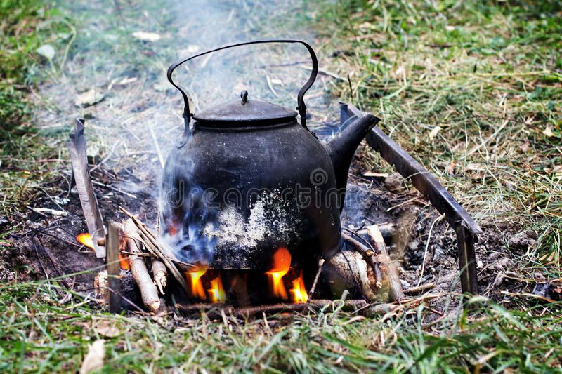 Kettle over the fire. Hike, summer vacation, outdoor recreation, outdoor food. Tourist kettle over campfire royalty free stock images