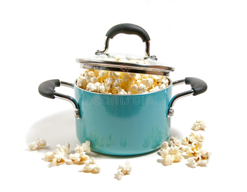 Kettle popcorn. Freshly popped corn overflowing in kettle isolated on white stock image
