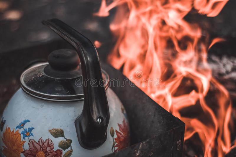 Kettle stands near the fire, heated for tea or coffee stock photo