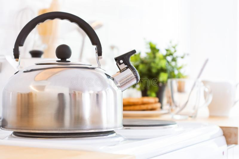 Kettle on the stove in the kitchen. Good morning or breakfast concept. Metal kettle with a whistle stands on an electric stove in the kitchen. Good morning or stock photography
