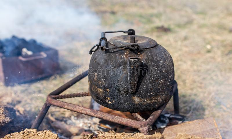 Kettle with water on the fire in nature stock photography
