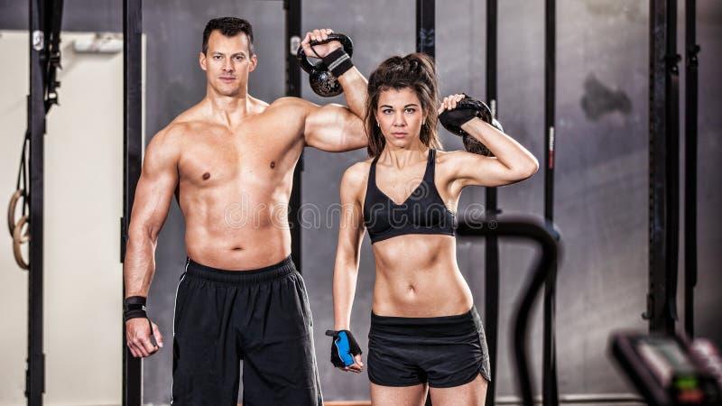 Kettlebell训练男人和妇女健身房的 库存图片