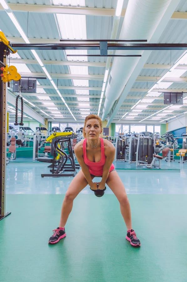 Kettlebell женщины поднимаясь в тренировке crossfit стоковые фото