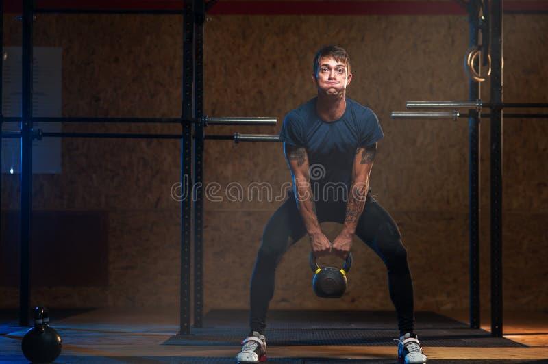 Kettlebell de elevación del atleta muscular de sexo masculino imagenes de archivo