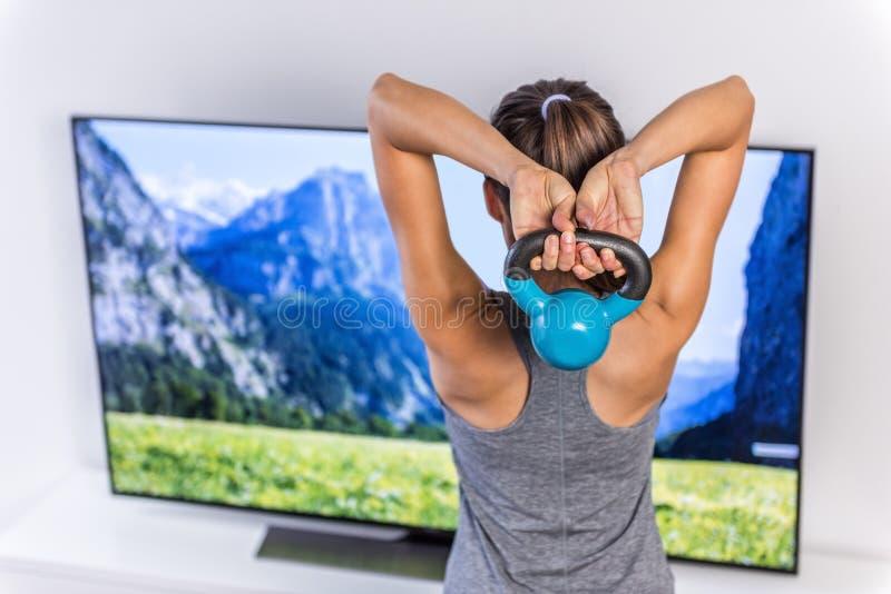 Kettlebell de elevación de la mujer casera de la aptitud que ve la TV fotos de archivo libres de regalías