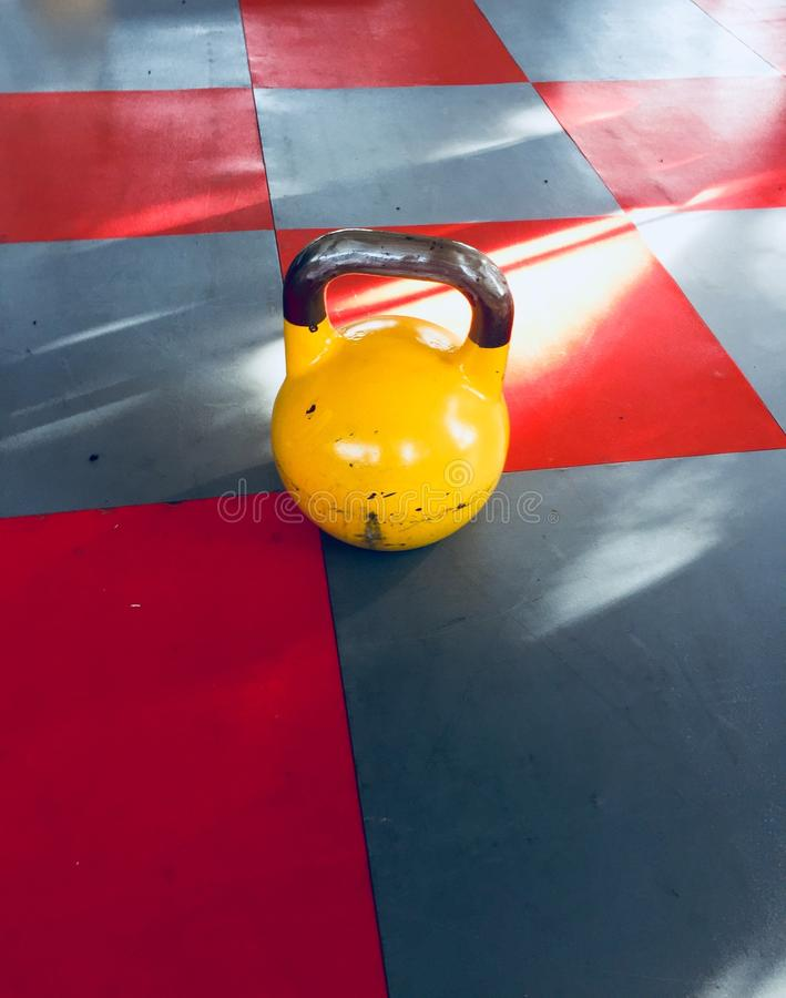 Kettlebell jaune sur le plancher - kettlebell d'isolement photographie stock
