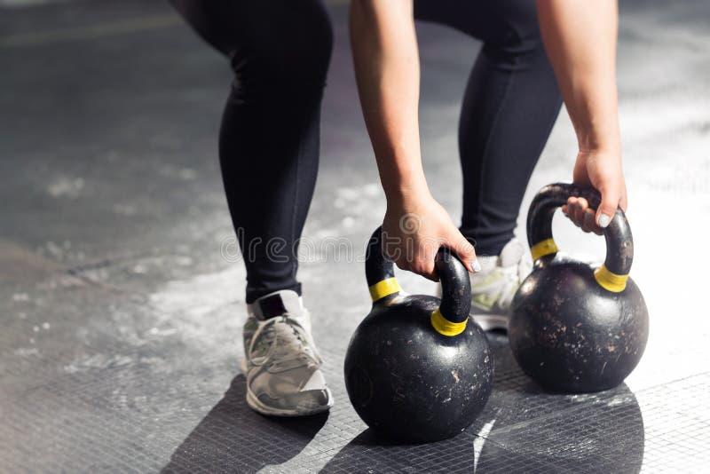 Kettlebell på golv Flickautbildning i idrottshall royaltyfri bild