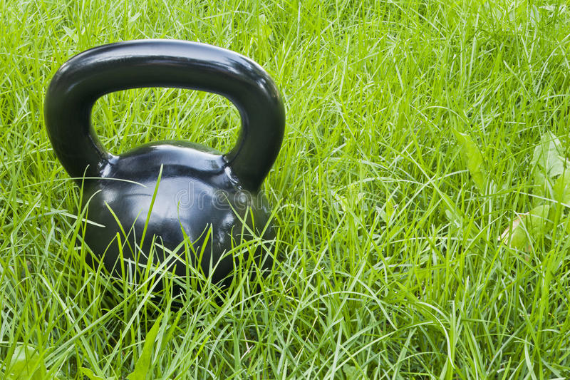 Kettlebell pesado del hierro en hierba imagen de archivo