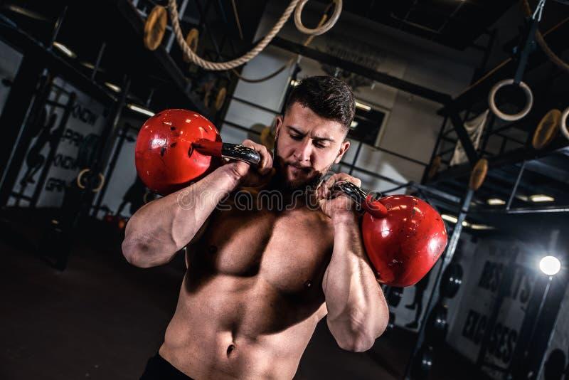 Kettlebell tränar i gymmet med en ung muskelsvettig man med muskler royaltyfri foto
