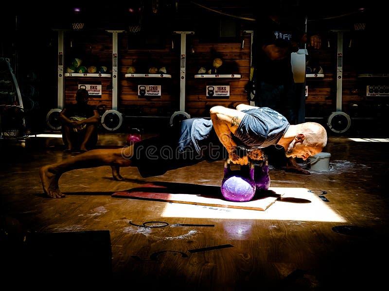Kettlebell trener Wykonuje Kettlebell odszczepiena rzędy fotografia stock
