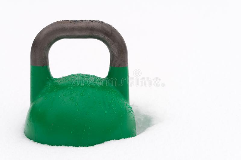Kettlebell verde do competiton na neve imagens de stock royalty free
