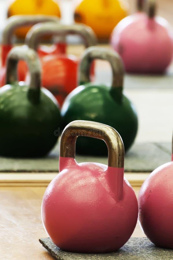 Kettlebells av olika färger och vikter på idrottshallgolv fotografering för bildbyråer