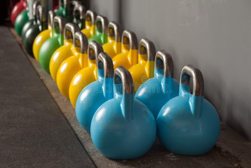 Kettlebells coloridos em seguido em um gym fotografia de stock royalty free