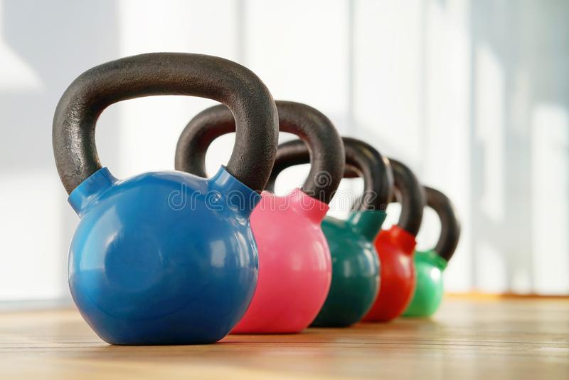 Kettlebells coloridos no gym fotografia de stock