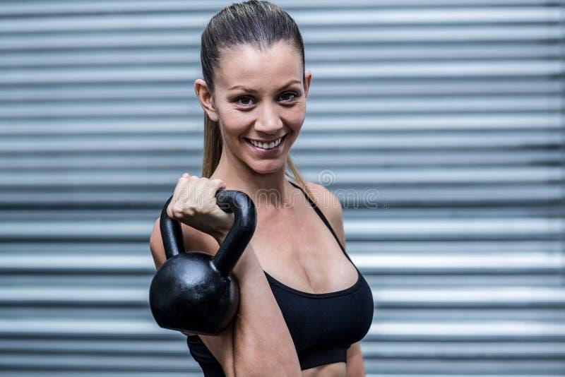 Kettlebells de elevación de una mujer muscular foto de archivo libre de regalías