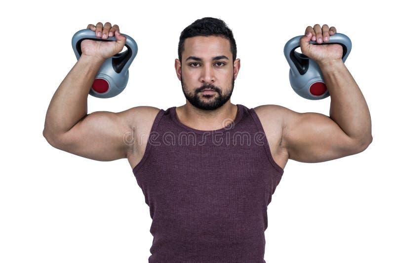 Kettlebells de elevación del hombre serio muscular imagenes de archivo