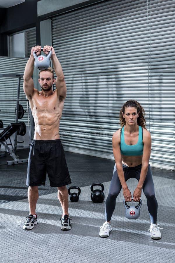 Download Kettlebells De Levage D'un Couple Musculaire Image stock - Image du route, muscle: 56490715