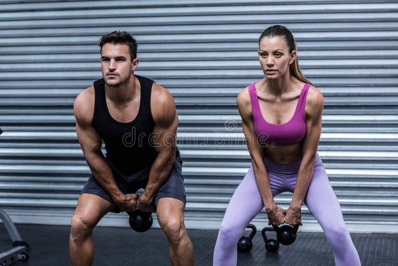 Kettlebells de levantamento de um par muscular fotos de stock royalty free