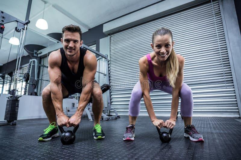 Kettlebells di sollevamento di una coppia muscolare fotografie stock