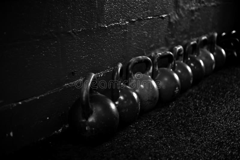 Kettlebells på golvet i en crossfitidrottshall B/W arkivfoto