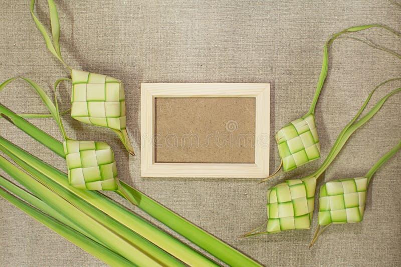 Ketupat与木制框架的米饺子在黄麻纹理背景 免版税库存图片