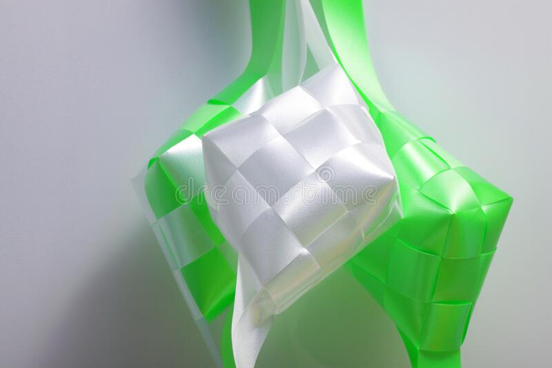 Close up shot of ketupat. Ketupat in Indonesian and Malay is a type of dumpling made from rice packed inside a diamond-shaped container of woven palm leaf pouch stock photo