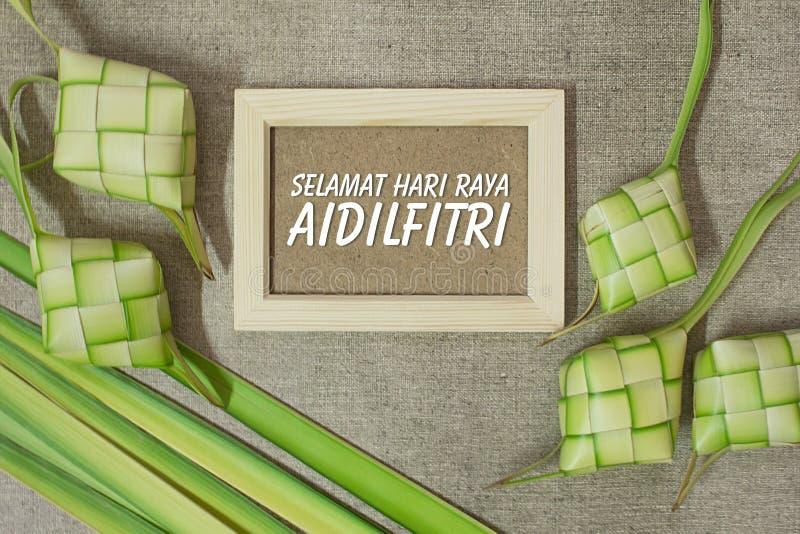 Ketupat rice dumpling with the wording of Selamat Hari Raya Aidilfitri on jute texture background. stock images