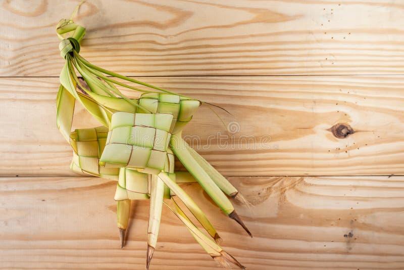 Ketupatzakken op Houten Achtergrond - die Ketupat is een type van bol van rijst wordt gemaakt binnen een diamantvormige container royalty-vrije stock foto's