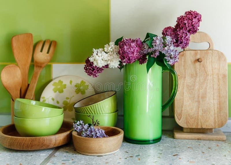 Keuken Ceramisch en Houten Vaatwerk, Boeket van Sering in de Groene Plastic Waterkruik royalty-vrije stock foto