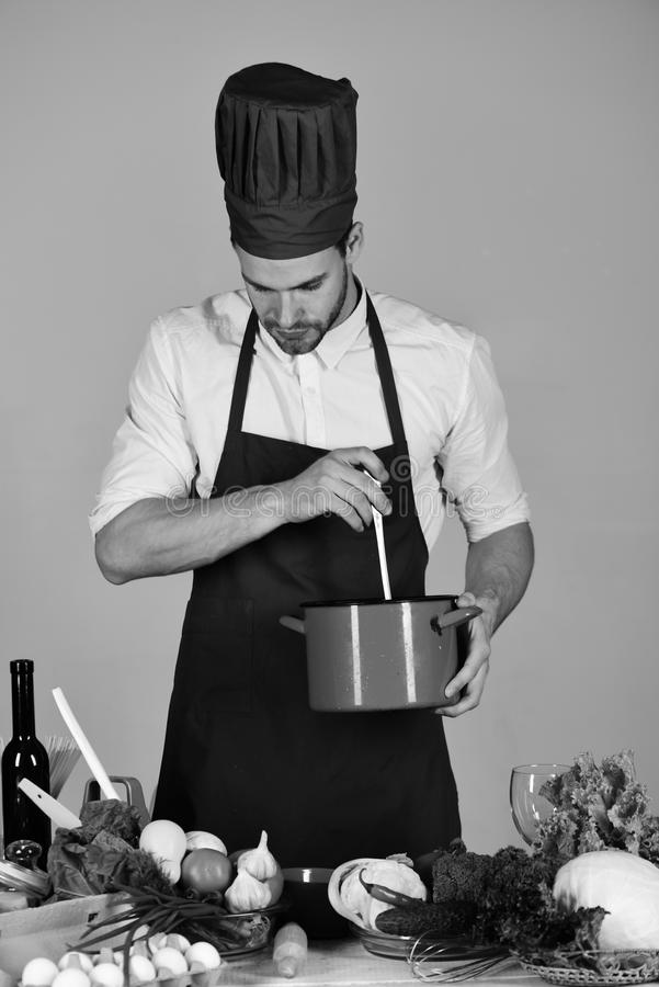 Keuken en professioneel het koken concept De chef-kok met bezig gezicht houdt rode steelpan op grijze achtergrond stock foto