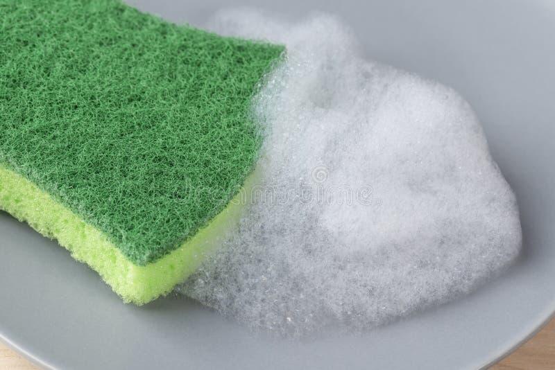 Keuken groene spons met schuimdetergens op een grijze plaat stock fotografie