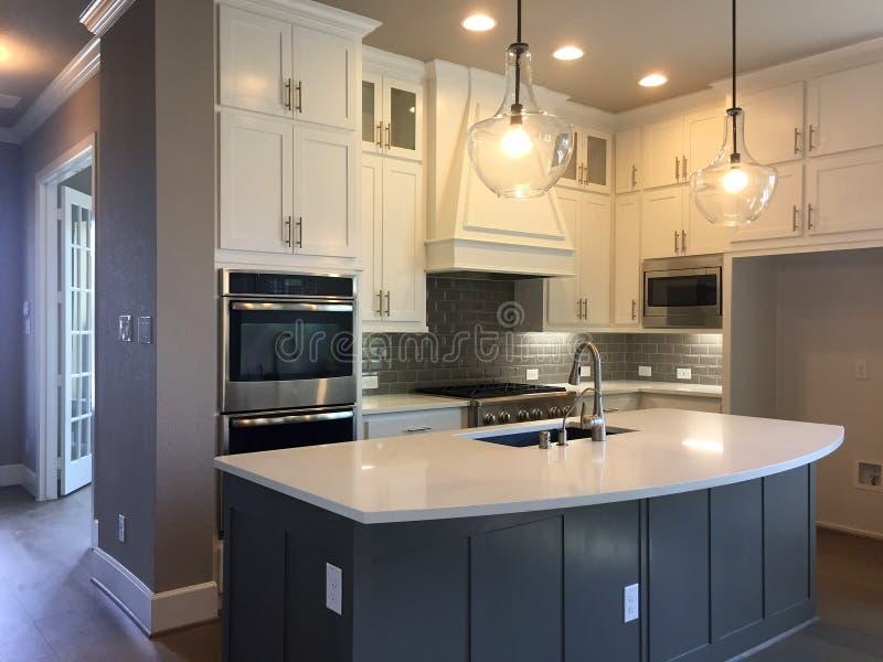 Keuken met eiland tegenontwerp in een nieuw huis stock fotografie