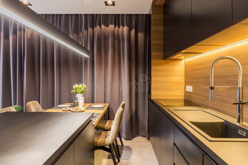 Keukenbinnenland met donkere meubilair, gordijn en eettafel w royalty-vrije stock foto