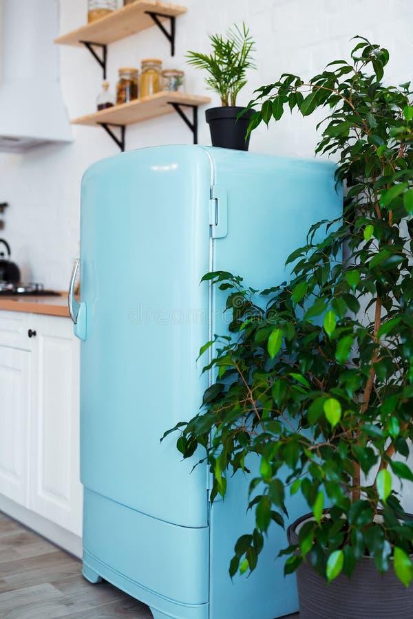 Keukenbinnenland in witte geweven kleuren met blauwe moderne retro koelkast en rustieke bakstenen muur Verticale stillevenfoto stock fotografie
