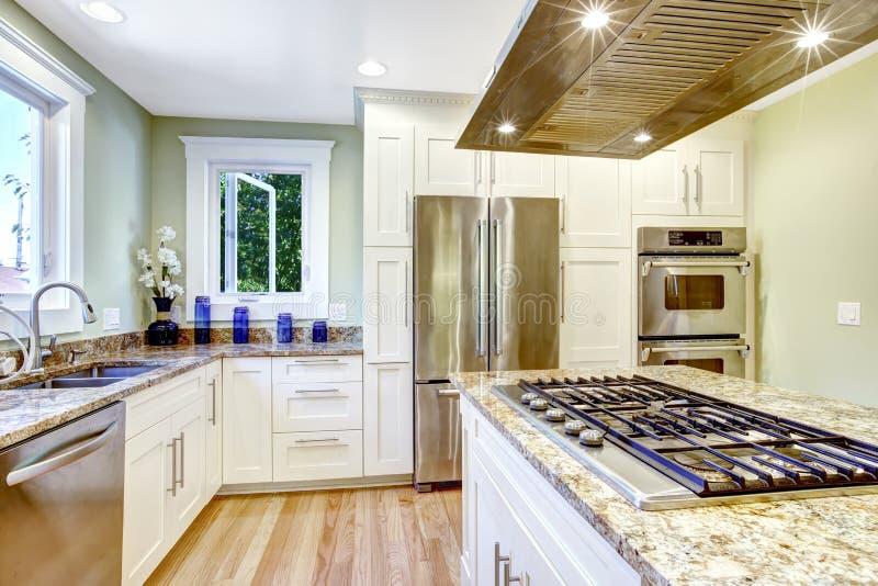 Keukeneiland met ingebouwd fornuis, granietbovenkant en kap stock afbeeldingen