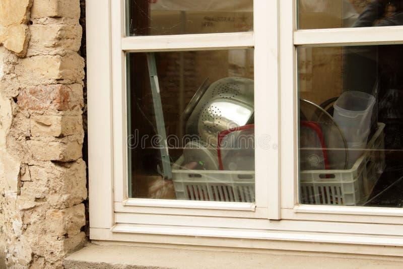 Keukengerei drogen in het keukenvenster met reflectie van buitenaf stock afbeelding