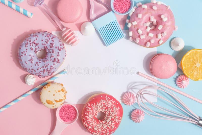 Keukengerei en hulpmiddelen, gebakjes en snoepjes op een roze en blauwe achtergrond Hoogste mening De ruimte van het exemplaar stock afbeelding