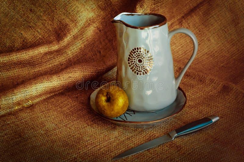 Keukengerei voor dorpsbewoners Nutrmort met kruiken, een appel en een mes Warme stoffenachtergrond De herfsttonen Rustieke stijl royalty-vrije stock fotografie