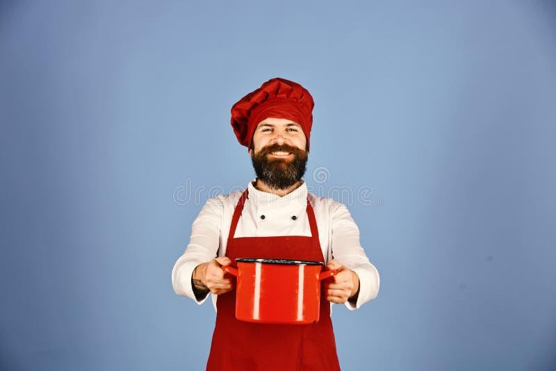 Keukengereiconcept Kok met vrolijk gezicht in eenvormig Bourgondië stock foto