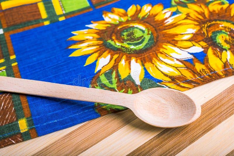 Keukenhanddoek en houten lepel aan boord royalty-vrije stock afbeeldingen