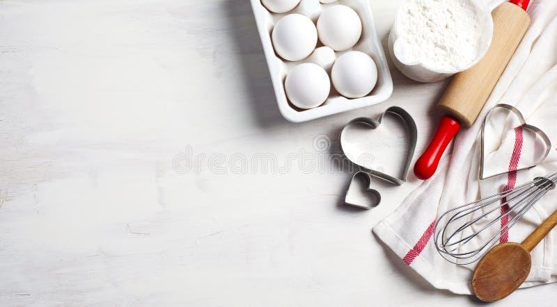Keukeningrediënten, keukenartikelen en voedingsmiddelen voor het bakken Keukengerei, meel en eieren stock fotografie