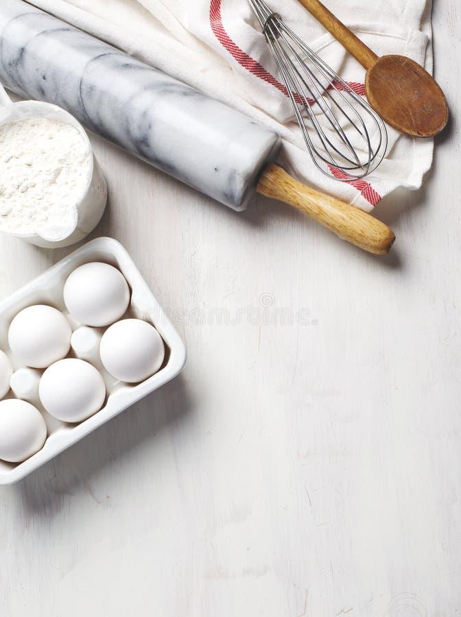 Keukeningrediënten, keukenartikelen en voedingsmiddelen voor het bakken Keukengerei, meel en eieren stock afbeeldingen