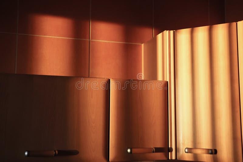 Keukenkasten in de stralen van de het plaatsen zon stock fotografie