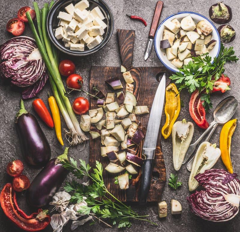 Keukenlijst met gehakte aubergine op houten scherpe raad met mes en diverse vegetarische kokende ingrediënten voor gezonde eati royalty-vrije stock afbeelding